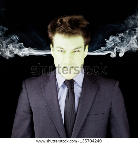 Furious businessman getting green isolated on black - stock photo