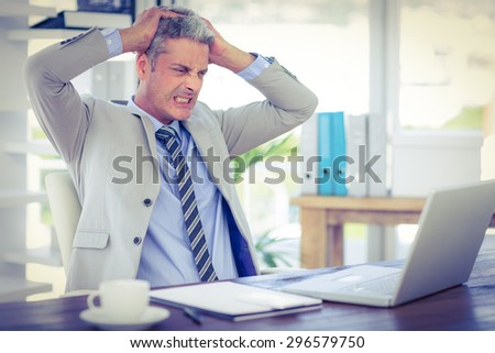 Furious businessman looking at laptop computer in office - stock photo