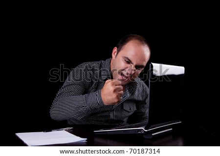 furious businessman looking to computer and taking notes, isolated on black background. Studio shot. - stock photo
