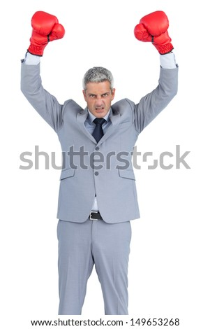 Furious businessman posing with red boxing gloves on white background - stock photo