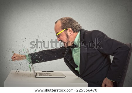 furious businessman throws a punch into computer screaming isolated grey office wall background. Negative human emotions, facial expressions, feelings, aggression, anger management issues concept - stock photo