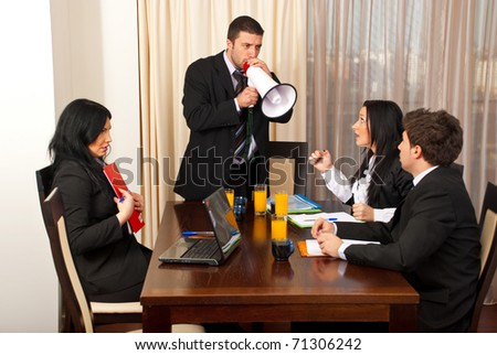 Furious chief shouting in megaphone to his employees at meeting - stock photo