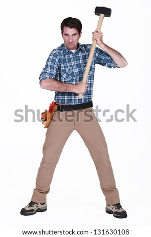 furious craftsman holding a hammer - stock photo
