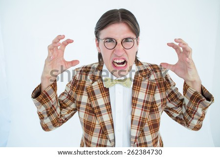 Furious geeky hipster looking at camera on white background - stock photo