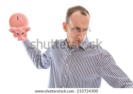 Furious isolated bald man smashing his piggy bank. - stock photo