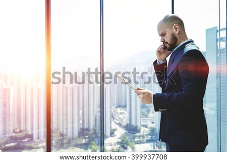 Furious male professional banker is read in internet via touch pad information about a sharp drop in currency at the market. Businessman is standing in office interior near window with copy space area