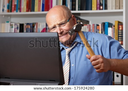 Furious man with bald patch hitting his computer with a hammer - stock photo