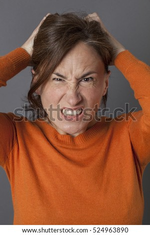furious middle aged woman pulling out her hair, losing temper, expressing irritation, frustration and stress, grey background