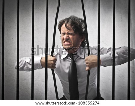 Furious strong businessman bending the bars of his prison - stock photo