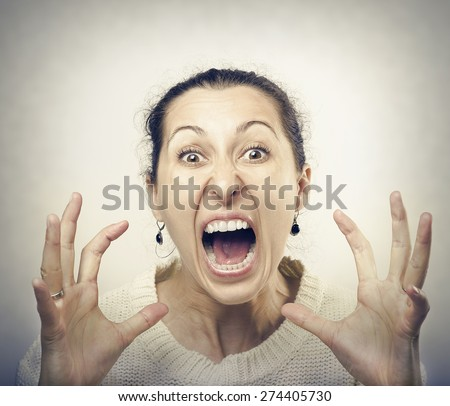 Furious woman screaming. Front view of furious brunette woman yelling at camera. - stock photo
