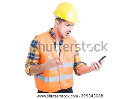 Furious young constructor yelling and showing rage while looking at his mobile phone because of a problem on white background - stock photo
