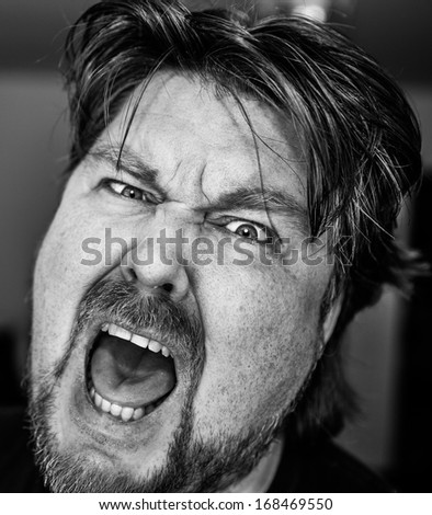 Furiously angry man shouting frantically with an intense look in his eyes from frustration in monochrome - stock photo