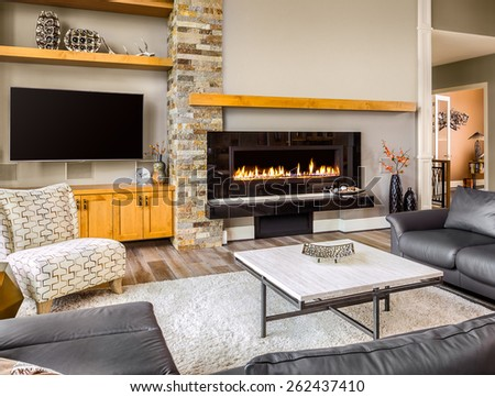 Furnished living Room in Luxury Home with Roaring Fireplace, TV, Coffee Table, Rug, and Wrap-Around Couch - stock photo