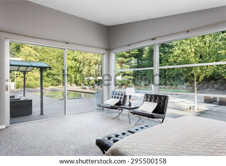 Furnished Master Bedroom in New Home with Amazing View of Backyard Patio with Trees and Pool, Accessible via Sliding Glass Door - stock photo