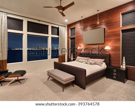 Furnished master bedroom interior in new home with amazing view of city lights and water at night