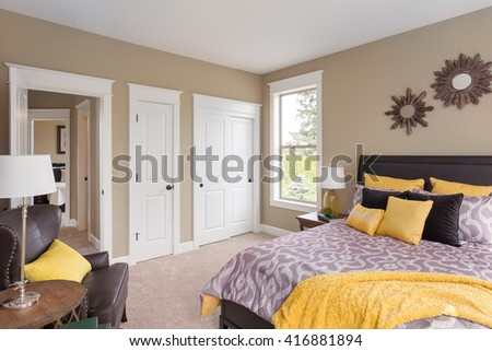 Furnished master bedroom interior in new home with colorful furnishings - stock photo