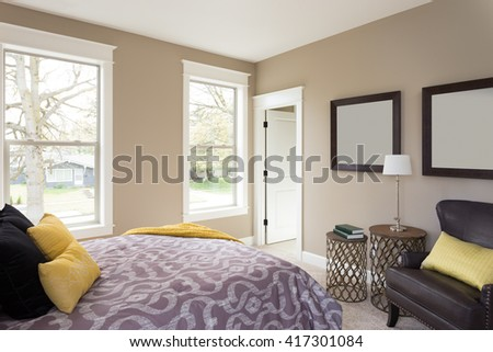 Furnished master bedroom interior in new home with colorful pillows, window view, and modern yet timeless feel - stock photo