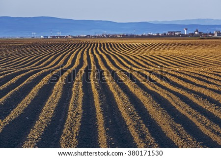 Furrows row pattern in a plowed land prepared for planting potatoes crops in spring in Transylvania region, Romania. - stock photo