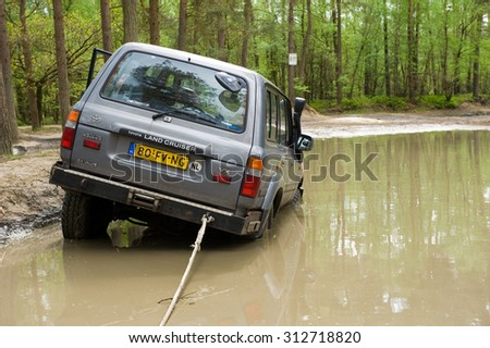 FURSTENAU, GERMANY - MAY 09, 2015: A Toyota Land Cruiser is stuck in a pond of water on a special off the road terrain for land cruisers and vehicles in Germany - stock photo
