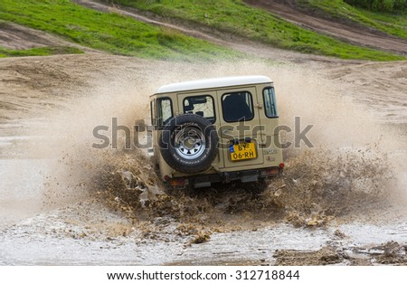 FURSTENAU, GERMANY - MAY 09, 2015: A Toyota 4-wheel drive is driving through a pond of water on a special off the road terrain for land cruisers and vehicles in Germany - stock photo