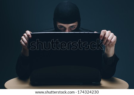 Furtive masked hacker accessing a laptop computer to steal data, plant malware or spy conceptual of cyber crime, online security and identity theft - stock photo