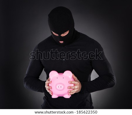 Furtive thief or burglar wearing a black outfit and balaclava making his escape through darkness stealing a pink piggy bank conceptual of theft of savings and investments - stock photo