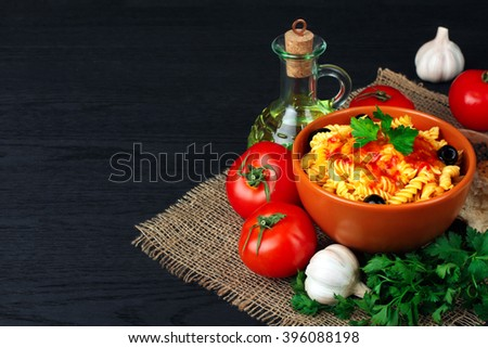 fusilli pasta and olives with parsley and ketchup in a bowl near to the tomatoes and parsley with chunks of fresh bread on a wooden black background - stock photo