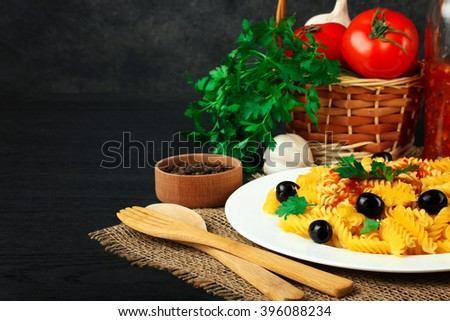 fusilli pasta and olives with parsley and ketchup in the plate near the wicker baskets with tomatoes and garlic on a wooden black background - stock photo