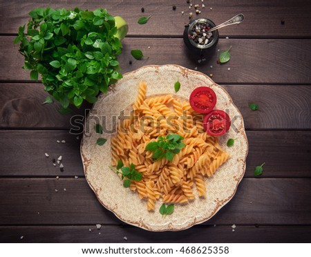 fusilli pasta in tomato sauce, tomatoes decorated with basil on a wooden background