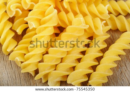 fusilli pasta on wood background