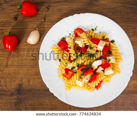 Fusilli pasta salad with cherry tomatoes and cheese in a plate on wooden table. top view