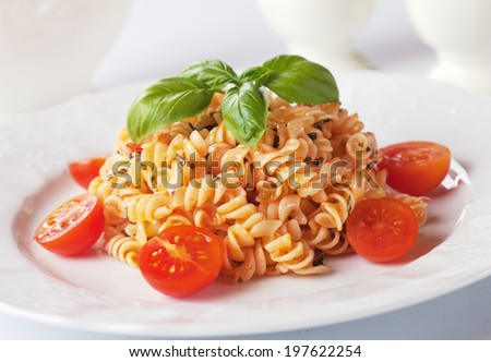 Fusilli pasta with basil and cherry tomato - stock photo