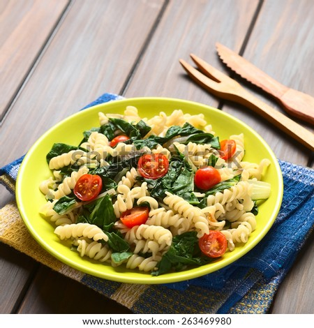 Fusilli pasta with chard leaves (lat. Beta vulgaris) and cherry tomatoes on plate with wooden fork and knife in back, photographed with natural light (Selective Focus, Focus in the middle of the dish) - stock photo