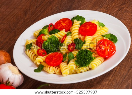 Fusilli pasta with cherry tomatoes and broccoli in a plate on wooden table