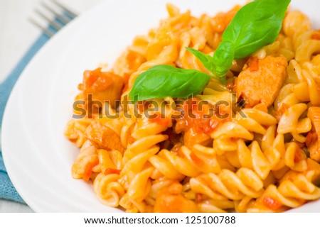 Fusilli pasta with chicken breast in tomato sauce - stock photo