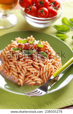 fusilli pasta with tomato sauce and basil leaves - stock photo