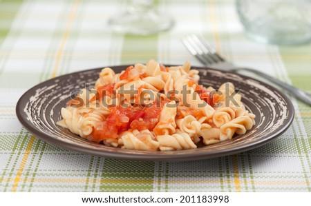 fusilli pasta with tomato sauce on a plate - stock photo