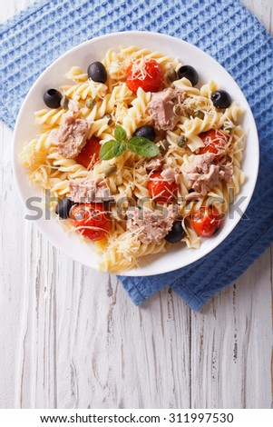 fusilli pasta with tuna, tomatoes and parmesan on the table. vertical top view - stock photo