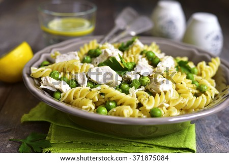Fusilli with chicken and green pea on rustic background. - stock photo