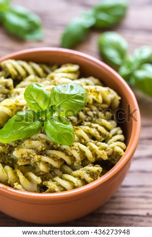 Fusilli with pesto sauce on the wooden background
