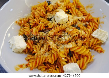 Fusilli with tomato sauce, parmesan, olives and pieces of cheese. Italian food. - stock photo