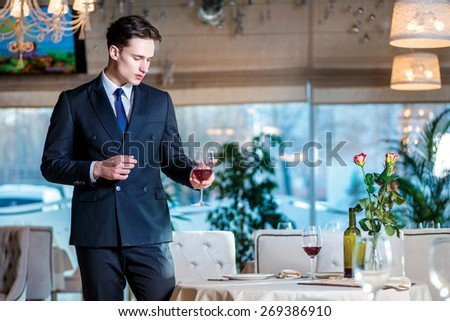 Future meeting. Young man businessman in formal wear standing in a restaurant while holding a glass of wine and looking forward - stock photo