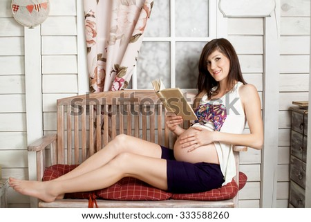 Future mother sitting on wooden bench and reading book indoors