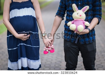 Future parents holding hands and a pair of little pink shoes - stock photo