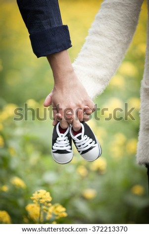 Future parents holding hands and a pair of little shoes over blur yellow flowers background - stock photo