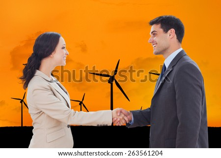 Future partners shaking hands against several wind turbines with a sunset - stock photo