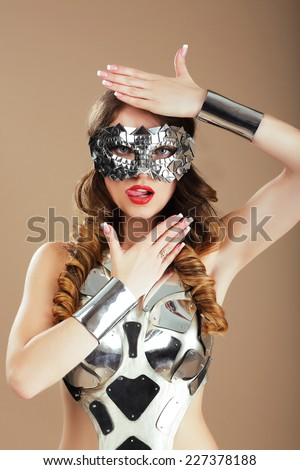 Futurism. Robotic Woman in Cosmic Mask and Metallic Stagy Costume Gesturing - stock photo