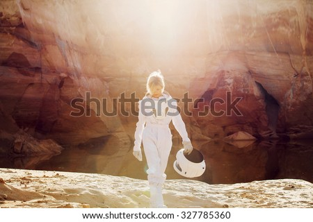 futuristic astronaut without a helmet in rays of another sun, image with the effect  toning - stock photo
