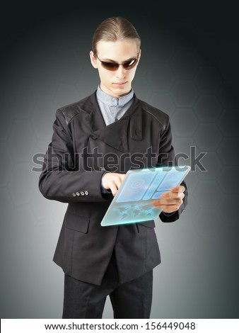 Futuristic businessman or secret agent working on his high-tech translucent tablet. - stock photo