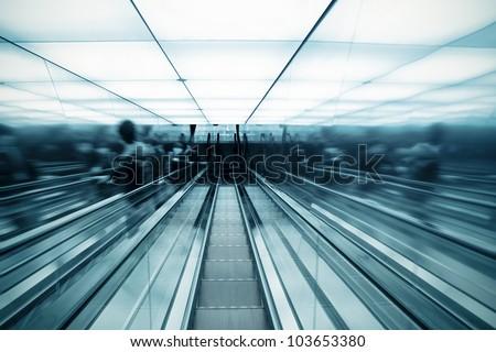 futuristic escalator and passenger motion blur - stock photo